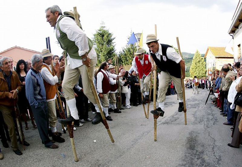 Villagers dressed in traditional clothing race on stilts through the Marche region town of Schieti